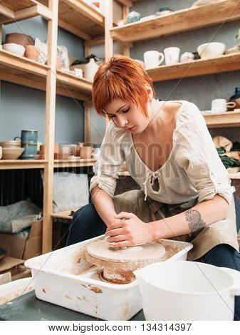 Woman works on potters wheel at studio. Plenty of pottery on background. Young red beautiful woman intently work on potters wheeln potters wheel