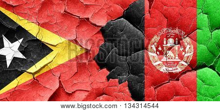 east timor flag with afghanistan flag on a grunge cracked wall