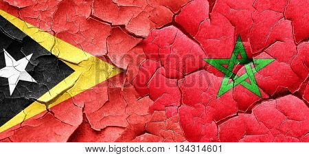 east timor flag with Morocco flag on a grunge cracked wall
