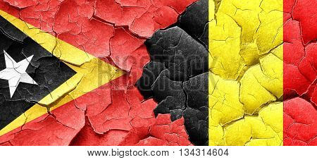 east timor flag with Belgium flag on a grunge cracked wall