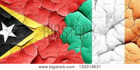 east timor flag with Ireland flag on a grunge cracked wall