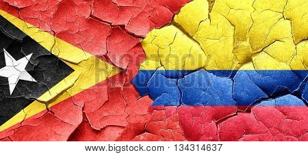 east timor flag with Colombia flag on a grunge cracked wall