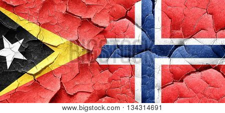 east timor flag with Norway flag on a grunge cracked wall