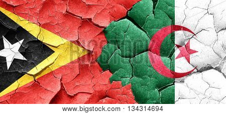 east timor flag with Algeria flag on a grunge cracked wall