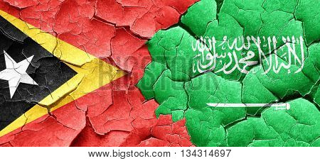 east timor flag with Saudi Arabia flag on a grunge cracked wall