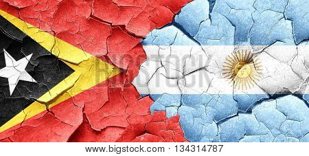 east timor flag with Argentine flag on a grunge cracked wall