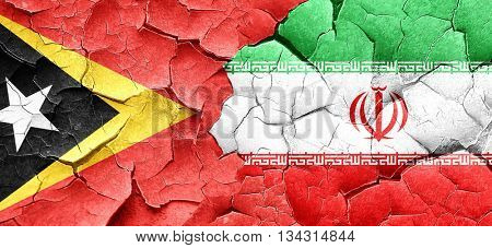 east timor flag with Iran flag on a grunge cracked wall