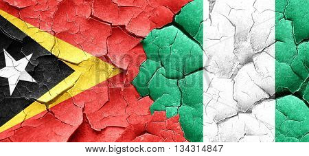 east timor flag with Nigeria flag on a grunge cracked wall