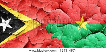 east timor flag with Burkina Faso flag on a grunge cracked wall