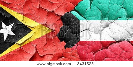 east timor flag with Kuwait flag on a grunge cracked wall