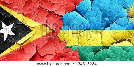 east timor flag with rwanda flag on a grunge cracked wall
