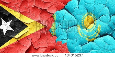 east timor flag with Kazakhstan flag on a grunge cracked wall