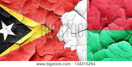 east timor flag with Madagascar flag on a grunge cracked wall