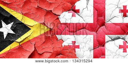 east timor flag with Georgia flag on a grunge cracked wall