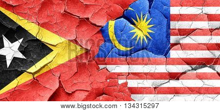 east timor flag with Malaysia flag on a grunge cracked wall