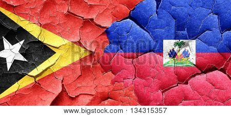east timor flag with Haiti flag on a grunge cracked wall