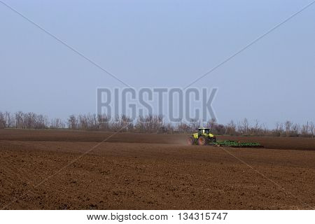 Tractor does harrowing and cultivation of arable land preparing it  for sowing