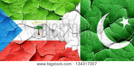 Equatorial guinea flag with Pakistan flag on a grunge cracked wa