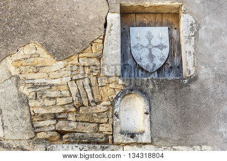 Old stone wall with niches and wooden shield stamp in one of the cities in Burgundy, France