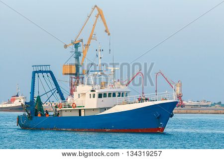 Blue fishing boat enters the port of Heraklion.
