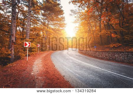 Beautiful asphalt road in orange forest at colorful sunrise in autumn. Crimean mountains.Travel background