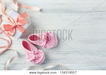 Beautiful composition with baby booties and gift box on wooden background
