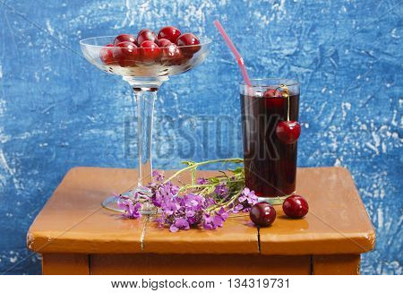 Still-life with cherries and cherry juice. A glass of cherry juice and cherry bouquet of wildflowers on a stool on a blue background.