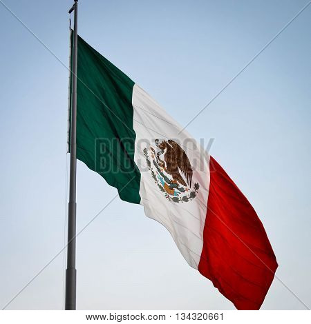 National flag of Mexico with the blue sky background flying over Zocalo square in Mexico city