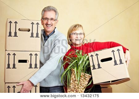 Two Senior People Carrying Packing Cases