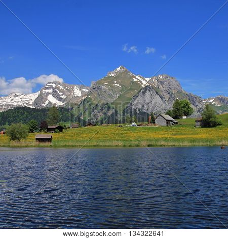 Spring scene in the Toggenburg valley Switzerland. Mt Saentis and other mountains of the Alpstein Range. Lake Schwendisee.