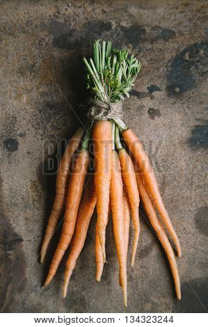 Bunch of fresh carrots on old grunge rusty backdrop top view copy space