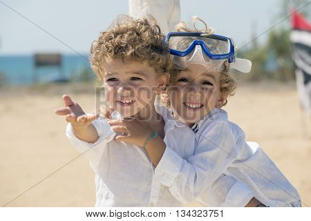 two blond brothers playing on the beach ina sunny day