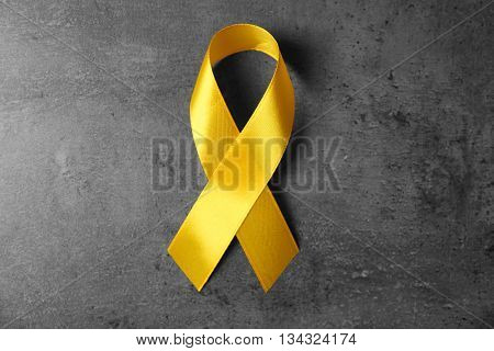 Yellow awareness ribbon on grey textured background