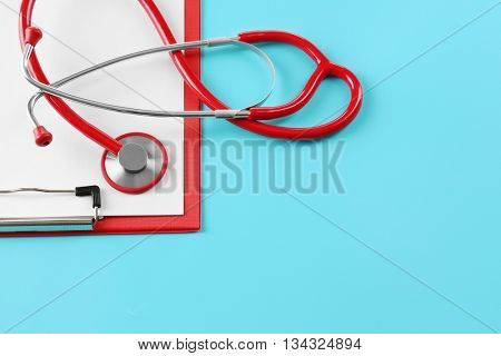 Red stethoscope with prescription on blue background