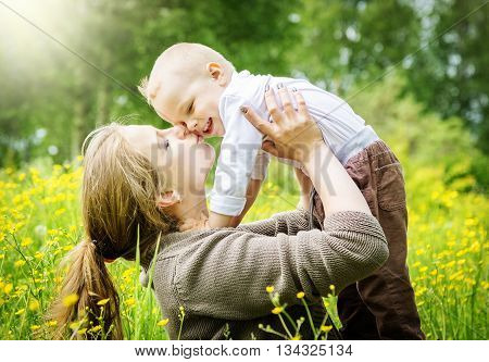Happy family, mother lifts her son and kisses him on nature background with sun rays
