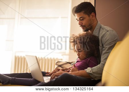 Dad and his little kid watching something on a laptop.