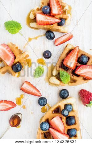 Home made Belgian waffles served on a white woodenl tray with berries , marple syrup and mint leaves, top view