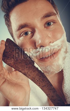 Young man with shaving cream foam having fun with machete large knife. Handsome guy removing beard hair. Skin care and hygiene humor. Instagram filter.