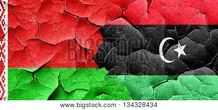 Belarus flag with Libya flag on a grunge cracked wall