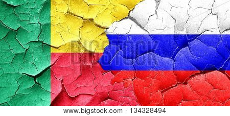Benin flag with Russia flag on a grunge cracked wall