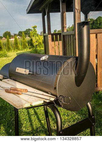 Black grill with chimney with wooden summer house in the background