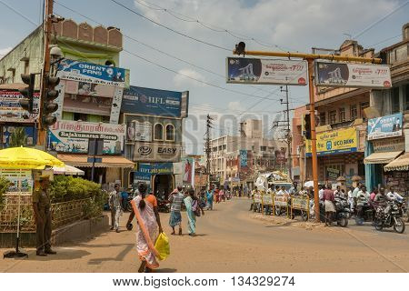 Chettinad India - October 17 2013: Busy intersection in Karaikudi city shows police traffic people billboards motorbikes shops and more.