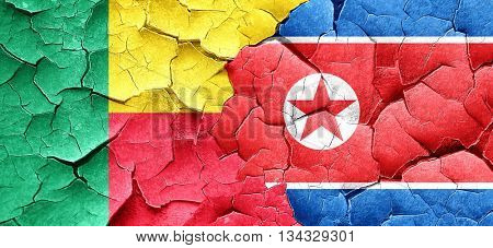 Benin flag with North Korea flag on a grunge cracked wall