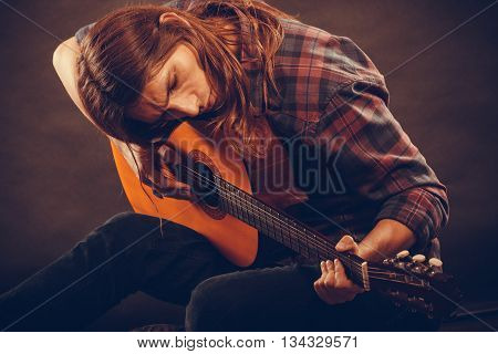 Music hobby concept. Young hippie is playing the guitar. Man is sitting on the floor and creating new song.
