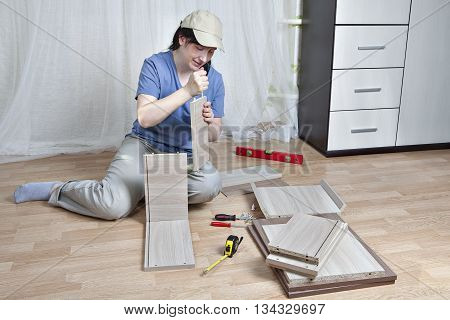 Furniture assembly woman lubricates surface of adhesive chipboard.
