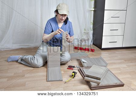 Woman fasten board drawer using glue assembly of wooden furniture at home.