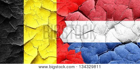 Belgium flag with Netherlands flag on a grunge cracked wall