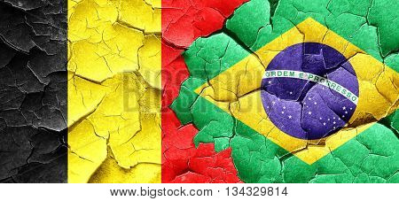 Belgium flag with Brazil flag on a grunge cracked wall