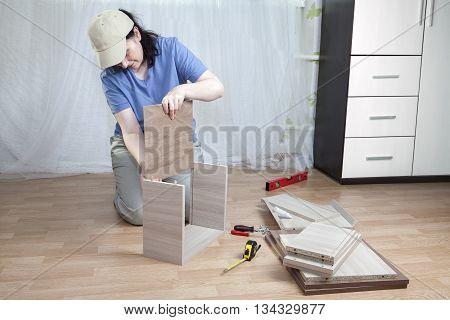 Installation of wooden furniture made of particle board in the home the woman assemble drawer.