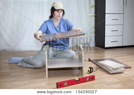 Self  assembly of furniture a housewife assembles nightstand in the interior of the apartment sitting on the floor.
